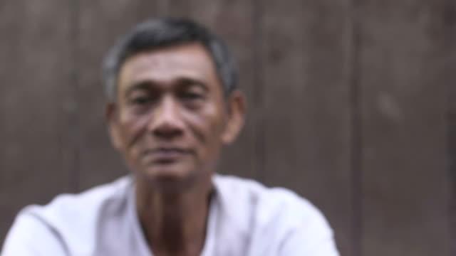 Serious Asian man looking at camera against brown wall video