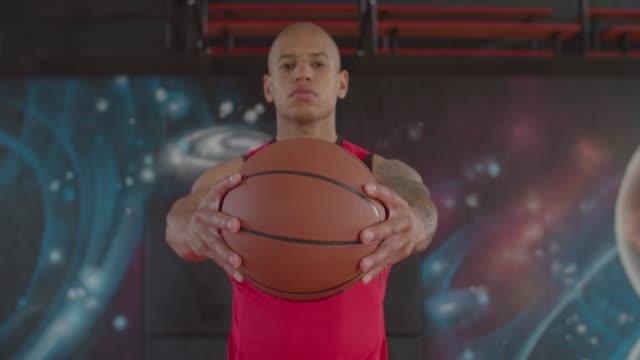 Serious backetball player holding basketball
