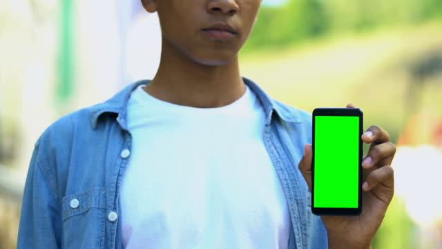 Serious black male teenager pointing finger into smartphone with green screen