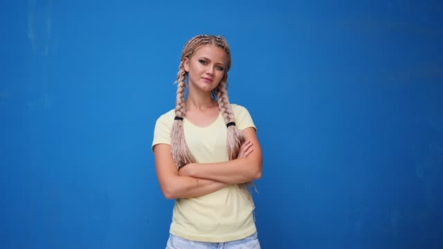 Serious blond hipster student woman looking at camera with arms crossed over blue background Serious blond hipster student woman looking at camera with arms crossed over blue background. pigtails stock videos & royalty-free footage