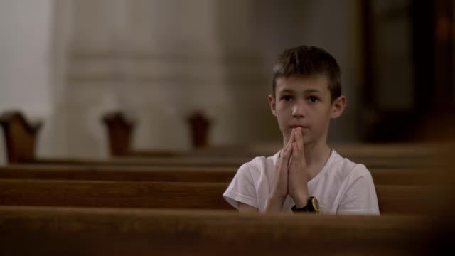 stockvideo's en b-roll-footage met ernstige jongen bidden in de kerk alleen - kerk