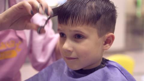 vidéos et rushes de sérieux garçon assis sur la chaise en tablier protecteur et avoir coupé les cheveux par le coiffeur - coiffure