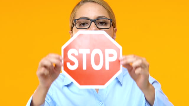 vídeos de stock e filmes b-roll de serious business woman showing stop sign into camera, sexual harassment on work - remote work