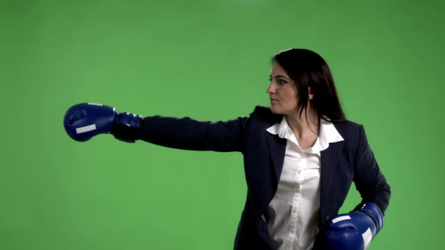Serious business woman with boxing gloves punching against green screen video