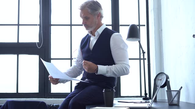 Serious businessman checking corporate paperwork correspondence Serious businessman checking corporate paperwork correspondence. Male entrepreneur reading documents, analyzing financial papers, preparing audit report at workplace. boss's day stock videos & royalty-free footage