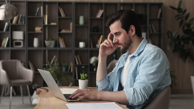 Serious businessman sit at desk in office texting on laptop