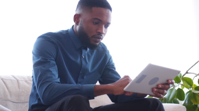 vídeos y material grabado en eventos de stock de empresario serio con tableta digital en la oficina - usar la tableta digital