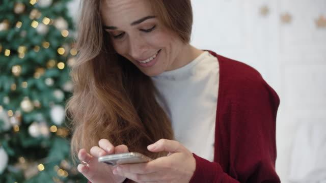 serious businesswoman searching presents on phone in christmas decorated home - surowy obraz filmowy filmów i materiałów b-roll