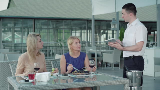ernster kaukasischer mann, der im restaurant im freien ordnung macht. porträt von professionellen männlichen kellner dienen reiche weibliche kunden in café. blonde frauen bestellen gerichte. lebensstil, freizeit, ernährung - bedienungspersonal stock-videos und b-roll-filmmaterial