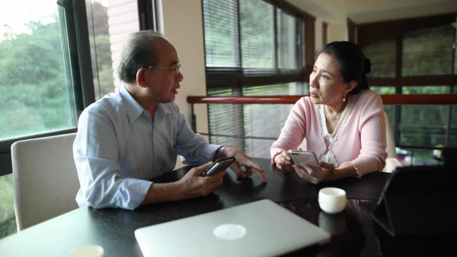 Serious Conversation Senior Asian couple having a conversation and using their phones at home. heterosexual couple stock videos & royalty-free footage