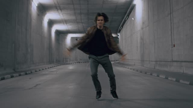 長い髪を持つ深刻なクールな若いヒップスターの男は、明るくコンクリートトンネルでエネルギッシュにダンスヒップホップです。彼は茶色の革のジャケットを着ている。 - スタイリッシュ点の映像素材/bロール