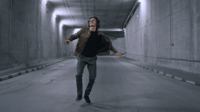 Serious Cool Young Hipster Man with Long Hair is Energetically Dancing Hip Hop in a Lit Concrete Tunnel. He's Wearing a Brown Leather Jacket.
