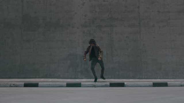 長い髪を持つ深刻なクールな若いヒップスターの男は、大きなコンクリートの壁の隣の通りに精力的にダンスヒップホップです。彼は茶色の革のジャケットを着ている。 - スタイリッシュ点の映像素材/bロール