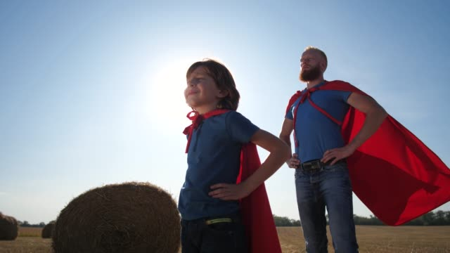 Serious dad and son in superhero pose on field Confident father and son in superhero pose standing with hands on hips and looking into distance during sunset. Redhead man and child stretching forward clenched fist and saying superhero's motto cape garment stock videos & royalty-free footage