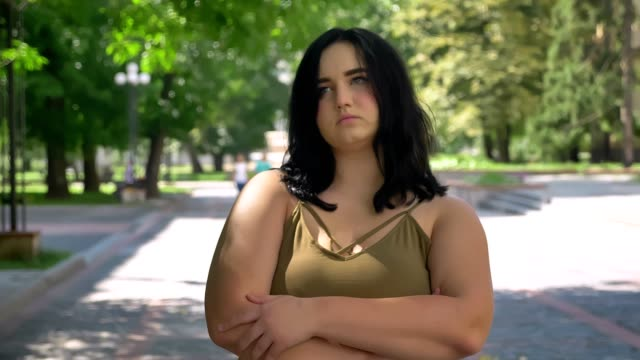 Serious depressed young pretty woman with obesity looking at camera, standing on street in park during sunny day