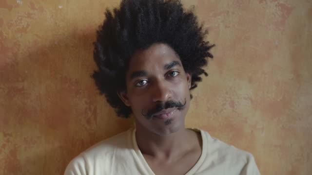 vídeos de stock e filmes b-roll de serious dominican young man looking at the camera - afro