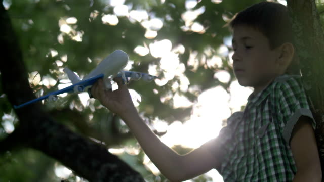 serious dreamer boy sitting on tree and playing with toy airplane video