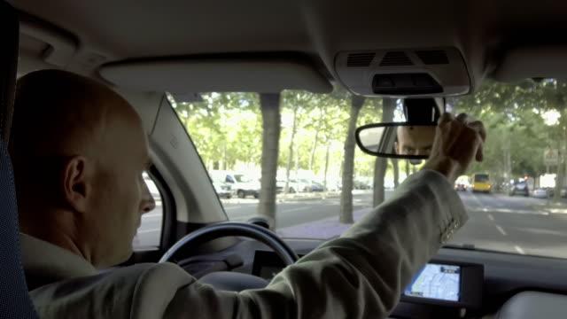 ciddi sürücü dikiz aynası araba yolculuğu sırasında ayarlama - ayarlamak stok videoları ve detay görüntü çekimi