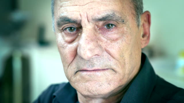 Serious elderly man looks to teh camera, closing his eyes close up on Serious elderly man looks to teh camera, closing his eyes depression land feature stock videos & royalty-free footage