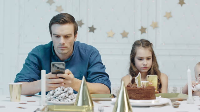 Serious father and daughter holding mobile cellphones on festive table.