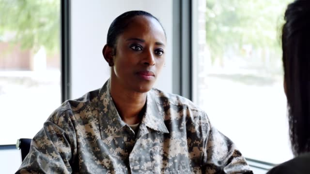 Serious female soldier talks with mental health professional Mid adult African American female soldier attentively listens and responds to advice given to her by an unrecognizable female counselor. military uniform stock videos & royalty-free footage