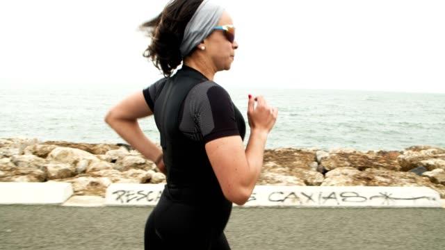 serious female triathlete training for marathon - triatleta video stock e b–roll