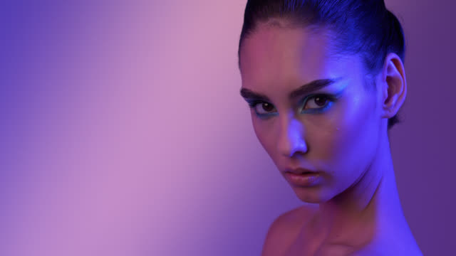 Serious girl looks defiantly with colored eye make-up. Pink and purple lighting.