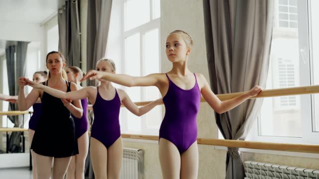 serious girls are practising arm movements during ballet lesson in studio. teacher professional ballerina is helping them correcting positions and giving instructions. - body abbigliamento sportivo video stock e b–roll