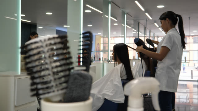 Serious hairdresser drying a customer's hair with a hairdryer and brush video