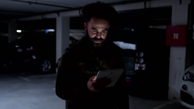 Serious hipster influencer holding a digital tablet Handsome modern hipster with a long beard and a pointy mustache holding a digital tablet. camouflage clothing stock videos & royalty-free footage