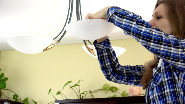 Serious housewife woman changing light bulbs video
