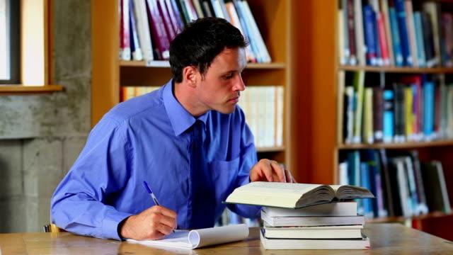 stockvideo's en b-roll-footage met serious lecturer preparing a class in the library - overhemd en stropdas