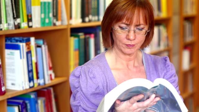 Serious librarian reading a book video