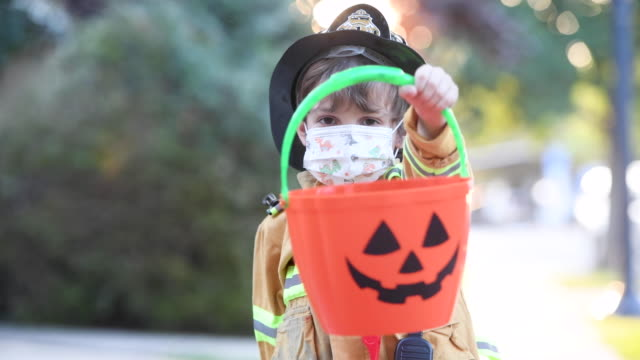 Serious little boy wearing a halloween fireman costume and a protective face mask looking at the camera holding a Jack o Lantern bucket Serious little boy wearing a halloween fireman costume and a protective face mask looking at the camera holding a Jack o Lantern bucket halloween covid stock videos & royalty-free footage