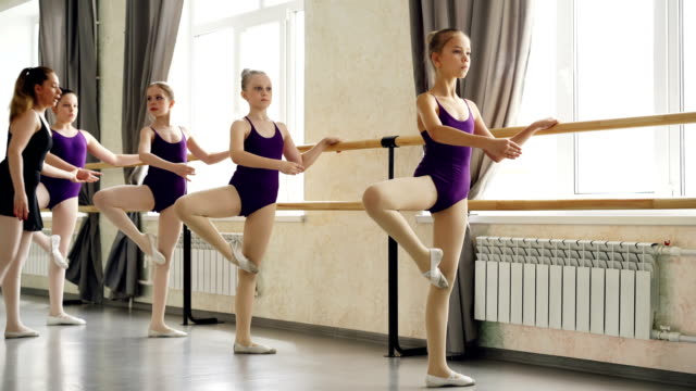 serious little girls are learning sequence of ballet positions at ballet class with helpful teacher. spacious light dancing hall with large windows and ballet barre is visible. - body abbigliamento sportivo video stock e b–roll