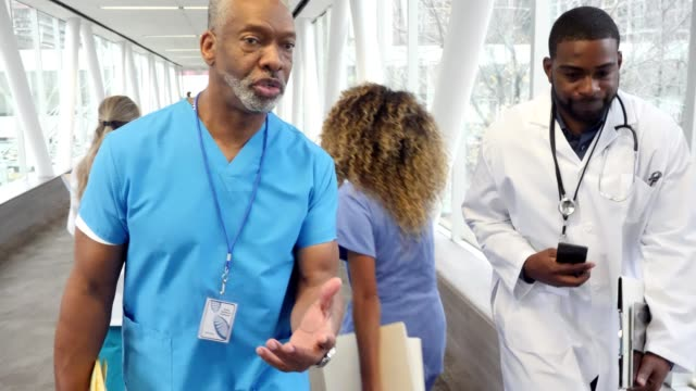 Serious male doctors walk quickly in hospital hallway Serious senior male doctor and mid adult male doctor talk as they walk quickly in an elevated hospital walkway. A female nurse moves past them as they walk in the hallway. medical building stock videos & royalty-free footage