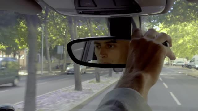 ciddi erkek sürücü araba ayna yolculuğu sırasında ayarlama - ayarlamak stok videoları ve detay görüntü çekimi