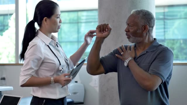Serious male patient discusses shoulder pain with doctor During a doctor appointment, a senior African American man raises his arm while touching his shoulder with his other hand. He is discussing his pain with a mid adult female orthopedic doctor. The doctor asks the patient questions about his pain as the patient places his arm in different positions. arm stock videos & royalty-free footage