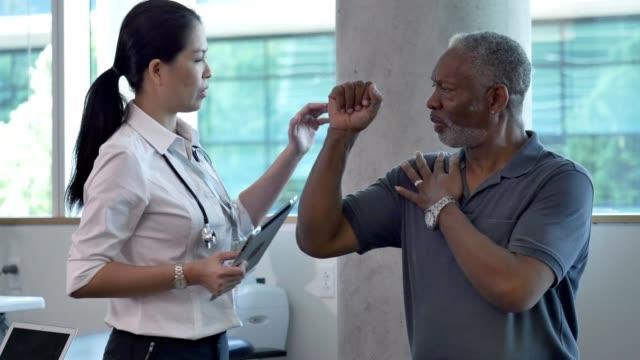 allvarlig manlig patient diskuterar skuldra smärta med läkare - axel led bildbanksvideor och videomaterial från bakom kulisserna