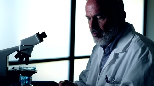 Serious male scientist uses digital tablet in laboratory