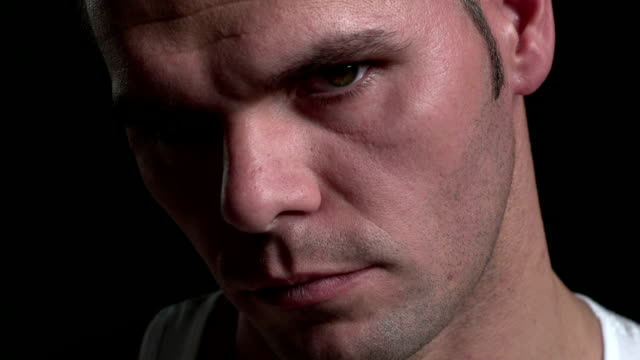 Serious man, looking up, black background video