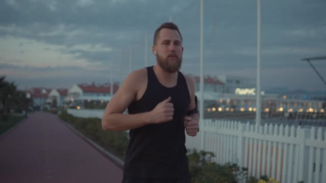 Serious man out jogging alone. - vídeo