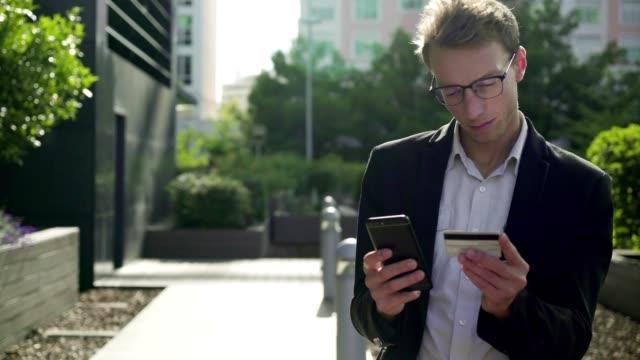 Serious man putting bank card data on phone, paying online