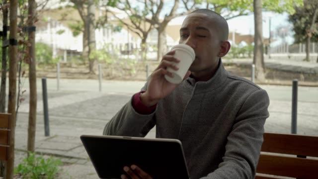 vídeos de stock e filmes b-roll de serious man using digital tablet and drinking coffee to go - esplanada portugal