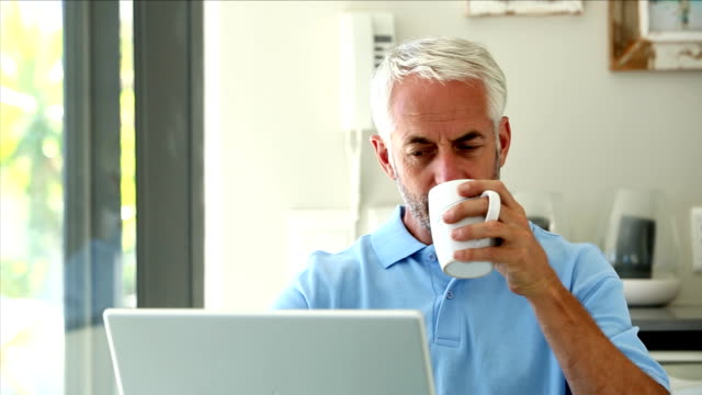 Serious man using his laptop while drinking a coffee video