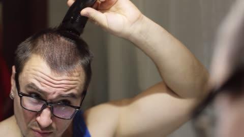 vidéos et rushes de un homme sérieux avec des lunettes regarde dans le miroir et rase les cheveux sur sa tête avec un trimmer professionnel. - coiffure