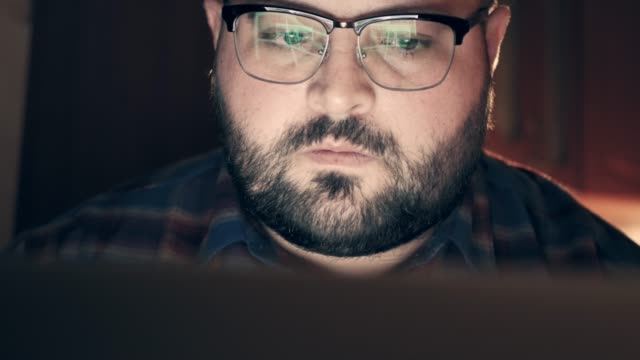 Serious man with reflection of laptop screen with website data in glasses working late, close up. Information analytic or internet marketing or coder developer portrait video