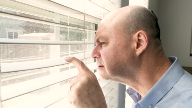 Serious mature man looking through his home window