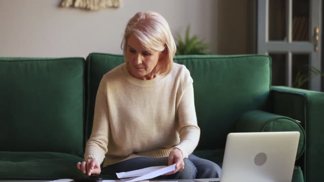 Serious mature woman calculating bills holding documents using laptop Serious middle aged mature woman calculating bills holding documents using laptop calculator for online payments, old lady paying with internet app on laptop doing paperwork manage household expenses hd format stock videos & royalty-free footage