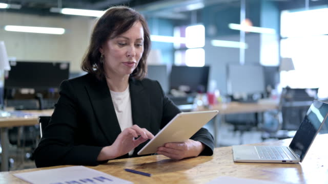 vídeos de stock e filmes b-roll de serious middle aged businesswoman working on tablet in office - senior business woman tablet